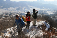 Hikers on the way up to a peak in Changping District, with snowy hills in the background