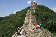 Hikers sitting on the unrestored wild wall below a Great Wall tower