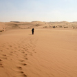 A person walks through the sandy dunes of the Tengger Desert