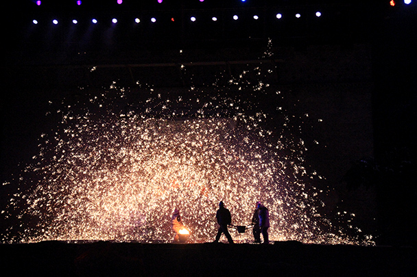 Two people carry in a bucket of molten iron; another flings it up to splash against the wall - Yu County CNY 2014 Overnighters, Part 2