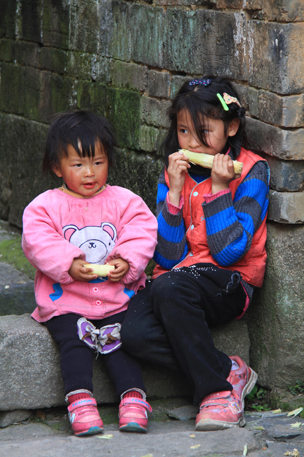Sisters snacking on some sugar cane - Wuyuan County, Jiangxi Province, 2014/03