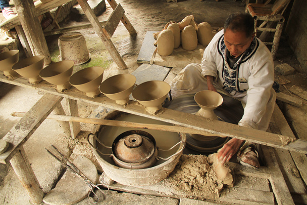 We visited a pottery factory to get a look at how they make the ceramic goods in the 'Porcelain Capital of China'. Here, bowls are being shaped by hand - Wuyuan County, Jiangxi Province, 2014/03