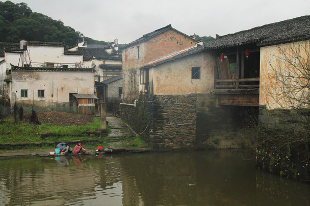 A covered bridge spans the stream, as local ladies do their washing - Wuyuan County, Jiangxi Province, 2014/03
