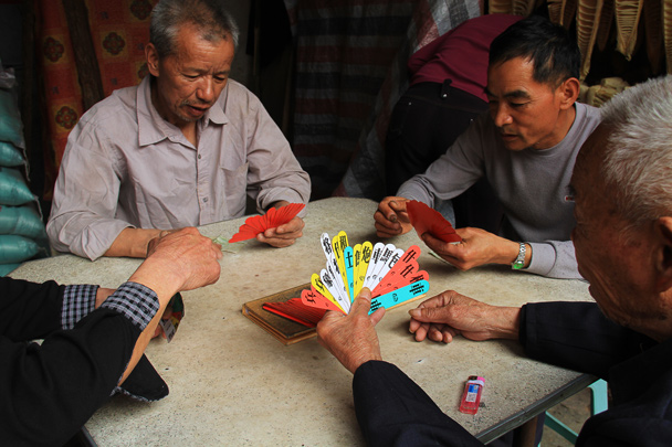 A traditional card game. The characters on the cards are the same as used for Chinese chess, if that helps - Hakka Tulou Clusters and Xiamen, Fujian Province, 2014/04