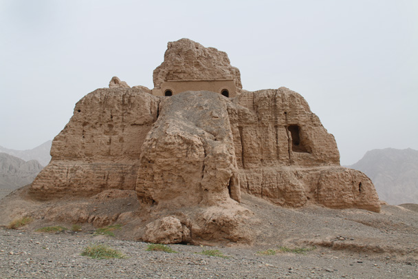 Another angle of the large tower at the center of the ruins, with layers of rammed earth visible where the brickwork has fallen away - Along the Silk Road from Korla to Kashgar, 2014/06