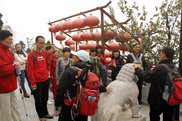 Huijie is talking about this stone lion and why it would have been placed here - Yajishan Taoist Temples hike, 2014/10