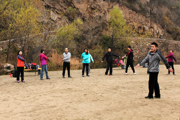 Everyone made a circle around the instructors from the Beijing Sports University as they led a stretching routine - CNCC teambuilding hike at the Little West Lake, 2014/10