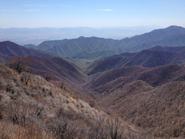 A view down a long valley, with the water of the Guanting Reservoir seen in the far distance - Dahaituo Mountain hike, 2015/04/25