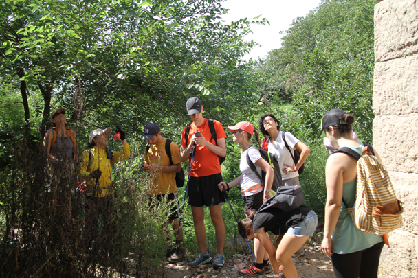 Staying out of the sun as Huijie talks about different features of the Great Wall - Walled Village to the Little West Lake, 2015/08/08