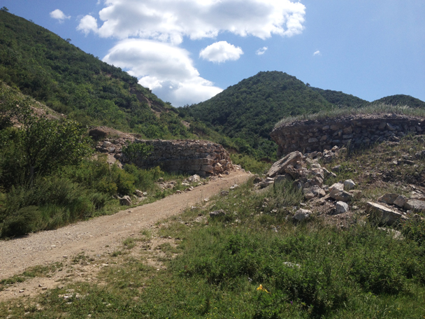 The Great Wall here dipped down to block off a pass. It's stripped bare of bricks here, which were used by villagers used to build houses - Shuitou Village Loop hike, 2015/08/22