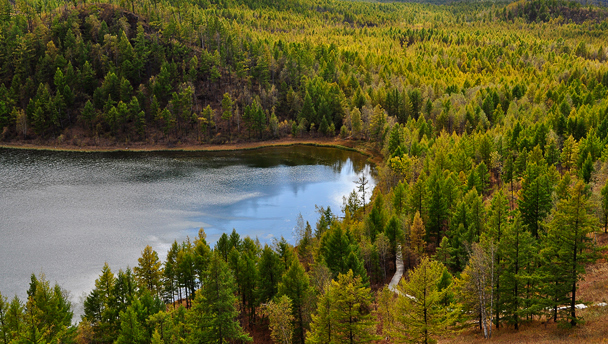 A crater lake surrounded by pines at the A'ershan National Forest Park, Inner Mongolia