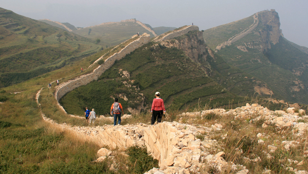 Hikers follow unrestored Great Wall on a bluff in Yanqing District