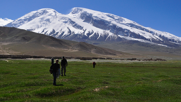 Hikers trek across grassy fields, with Mt. Muztagh-Ata in the background