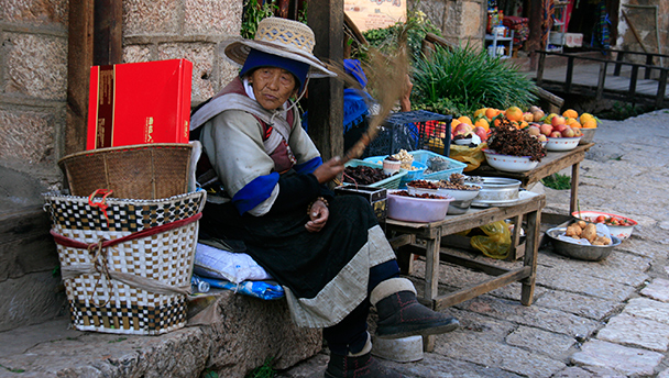 A Naxi matron selling snacks and trinkets