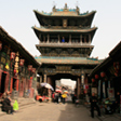 A arch with a tower on top spans a street in Pingyao, Shanxi.