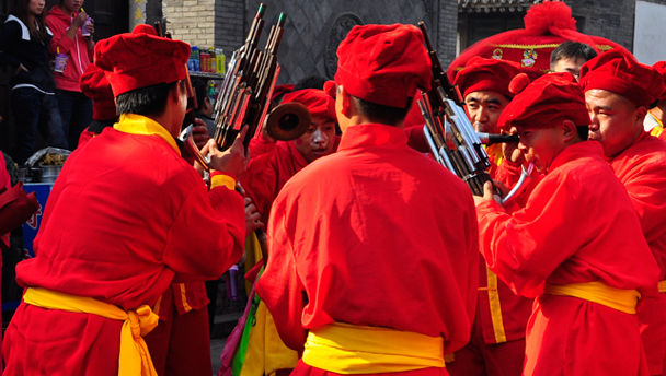 A band of street performers, dressed in red and yellow
