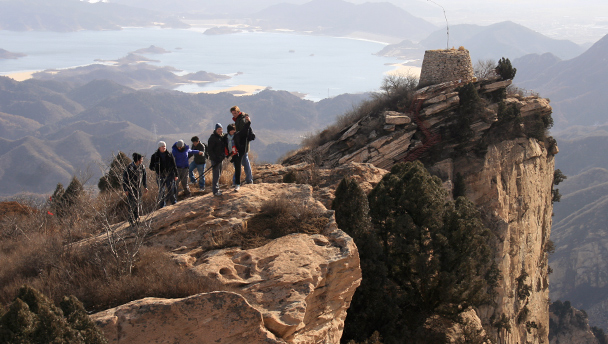 Hikers on a bluff, with the Round Tower and the Miyun Reservoir in the background