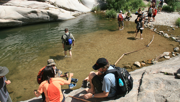 Hikers in and around a pool of water surrounded by boulders