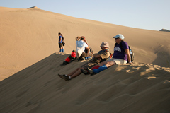 Hikers sitting on a high up sand dune