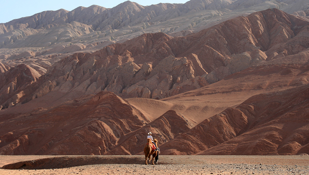 A person on camelback heading towards red-coloured mountains